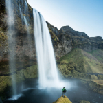 The ultimate adventure portrait in Iceland, posing with one of the planet's most famous waterfalls