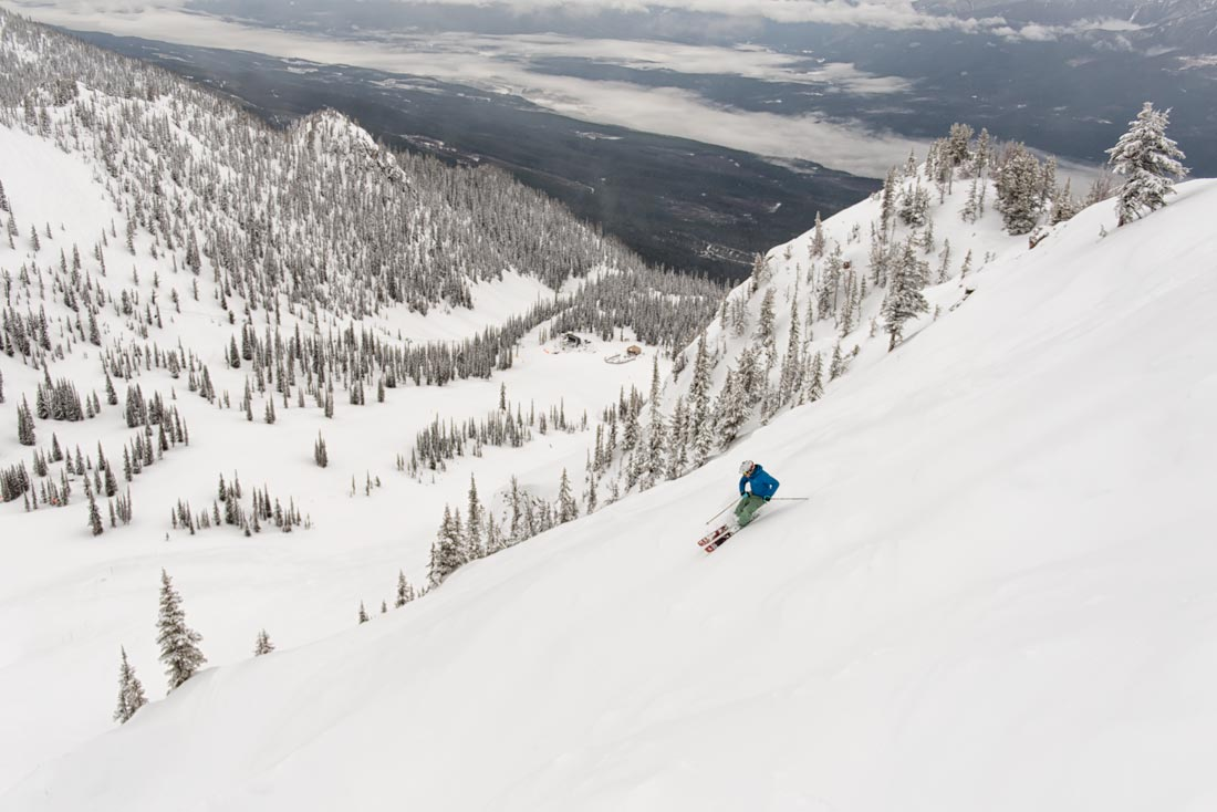A wide open alpine bowl with a lone skier descending towards the Stairway to Heaven chairlift