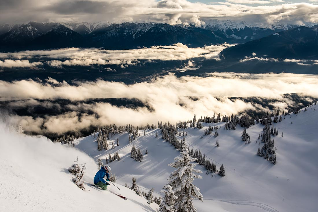 A skier arcs large turns down Kicking Horse Mountain, descending towards a landscape filled with dramatic clouds.