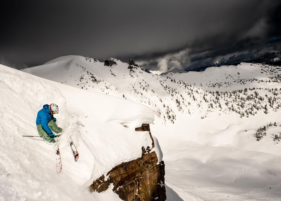 A skier slashes a turn above a large cliff at Kicking Horse