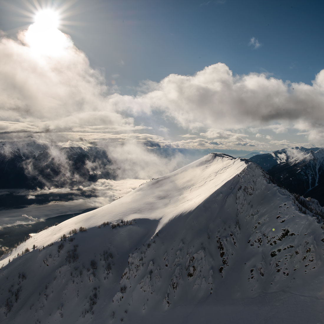 The sun cuts a dramatic shadow across the Purcell Mountains at Kicking Horse Resort