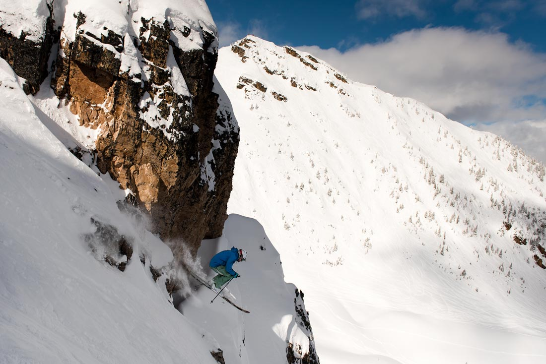 A skier hits a big air into a steep couloir in the Purcell Mountains