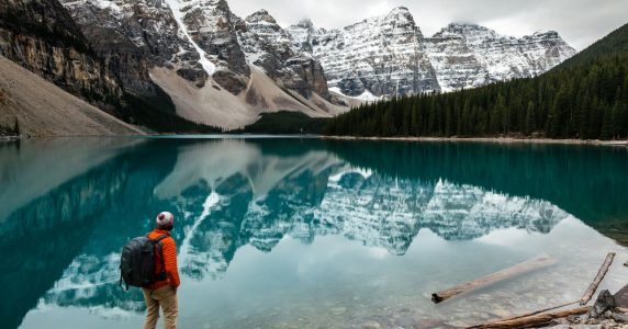A photographer stares down the length of Moraine Lake towards the Valley of the 10 Peaks