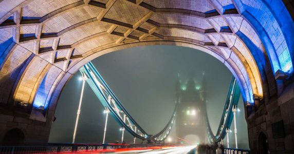 The tower bridge lit up at night in the fog. London, UK.