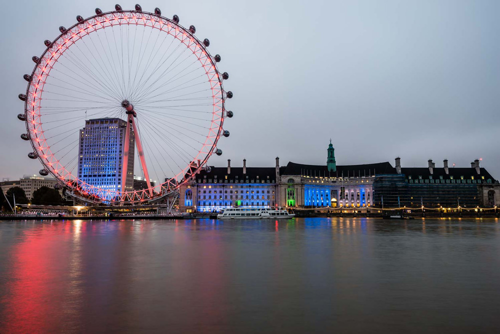 The London Eye lit up red in the pre dawn morning in Downtown London