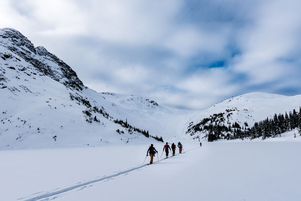 A group of alpine ski tourers head out on a high mountain traverse in British Columbia