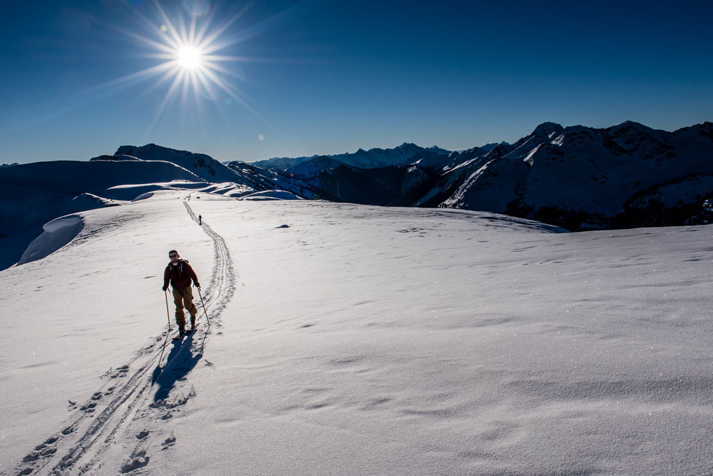 A skier tours into the sunlight at Whitecap Alpine