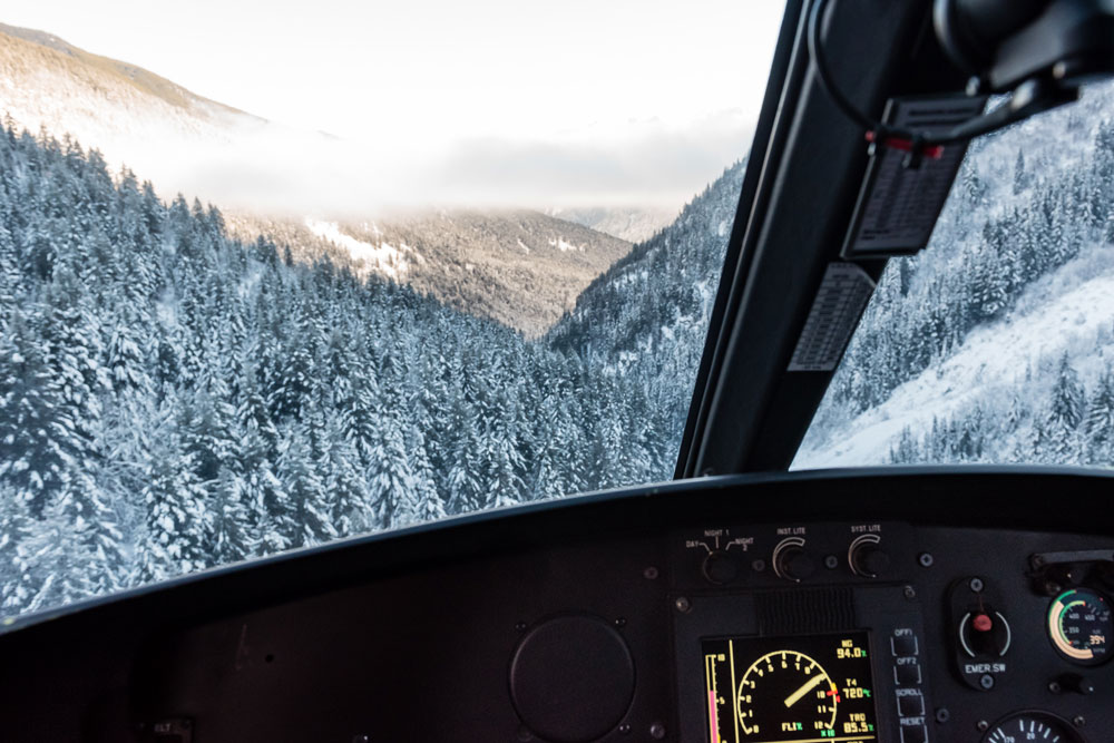 Looking through the helicopter windshield at the coastal mountain landscape.