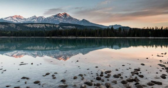 Warm morning light and light winds turn Lake Annette into the perfect mirror, showing off Pyramid Lake in the distance