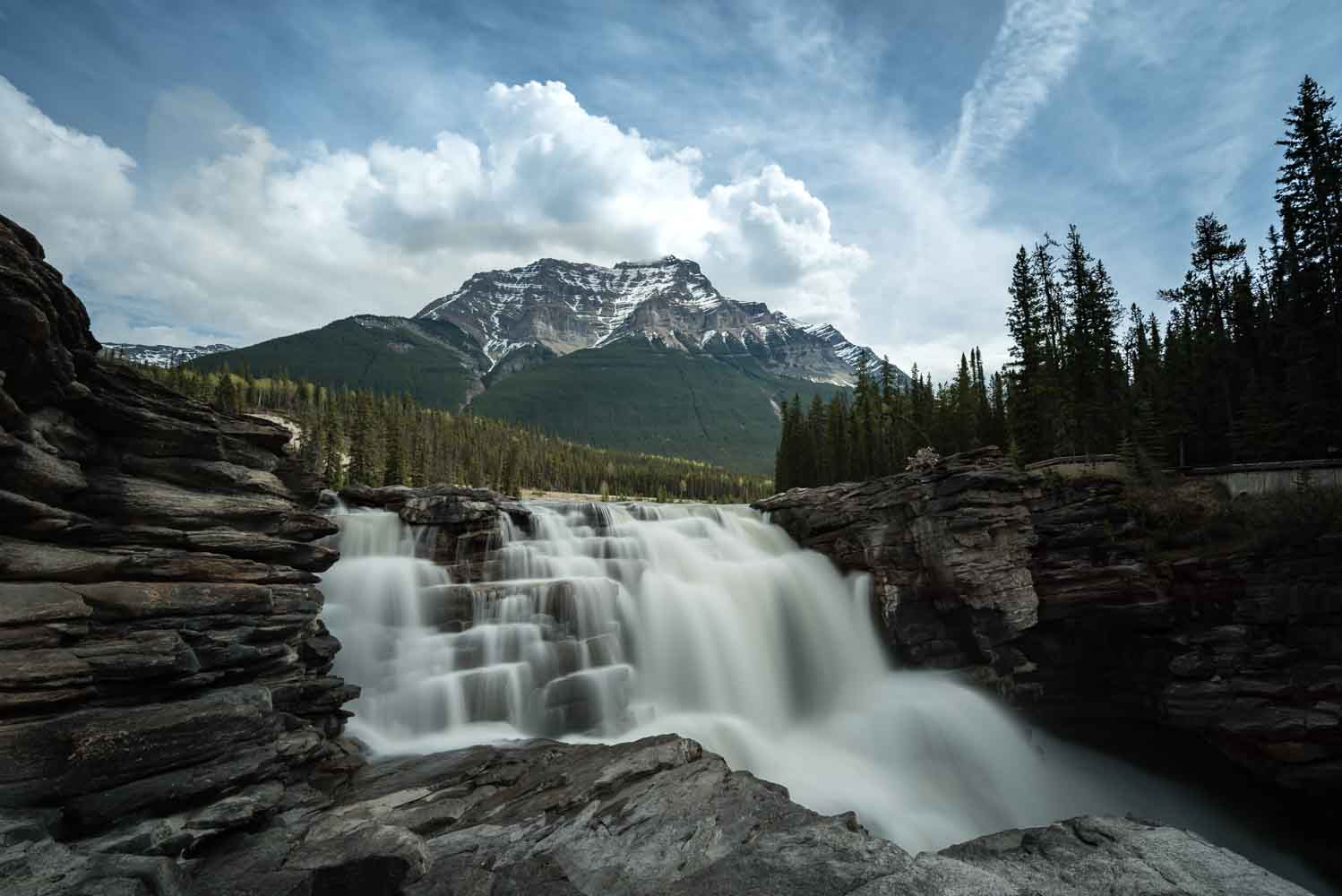 A long shutter speed makes the water at Athabasca Falls smooth and steady beneath Mt Kirkeslin in Jasper, Alberta