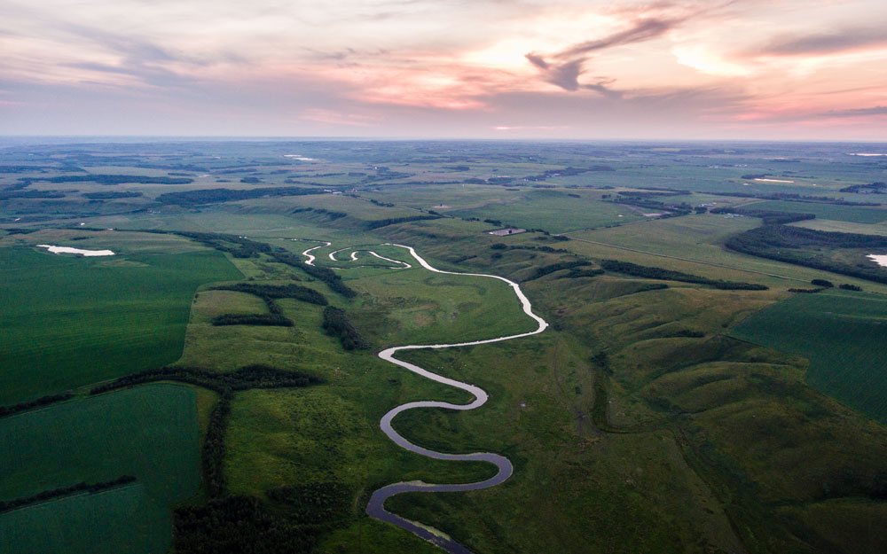 The Vermilion River looks something like a lazy lagoon on its way through the Canadian Prairies towards the west