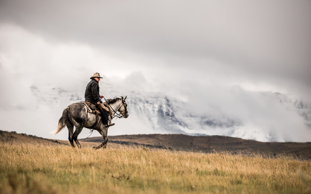 Randy, the owner of Sierra West Ranch, rides towards the snowy mountains on a cold travel alberta autumn day