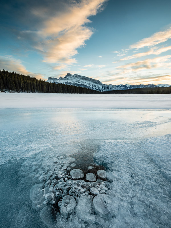 Alberta Winter Images: Ice bubbles, an annual phenomena on lakes throughout the Alberta Rockies adds an unusual twist to a classic image of Mt Rundle.