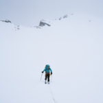 Kate descending towards the Louise and Richard Guy Hut in near white-out conditions.