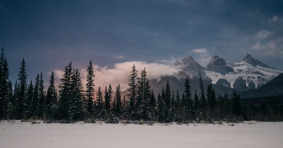 Dark skies above the Three Sisters in Canmore highlight the april desktop wallpaper series
