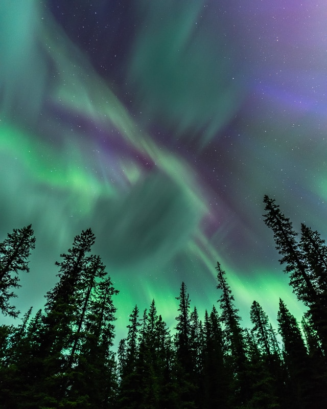 Northern lights soar overhead, illuminating the entire night sky.