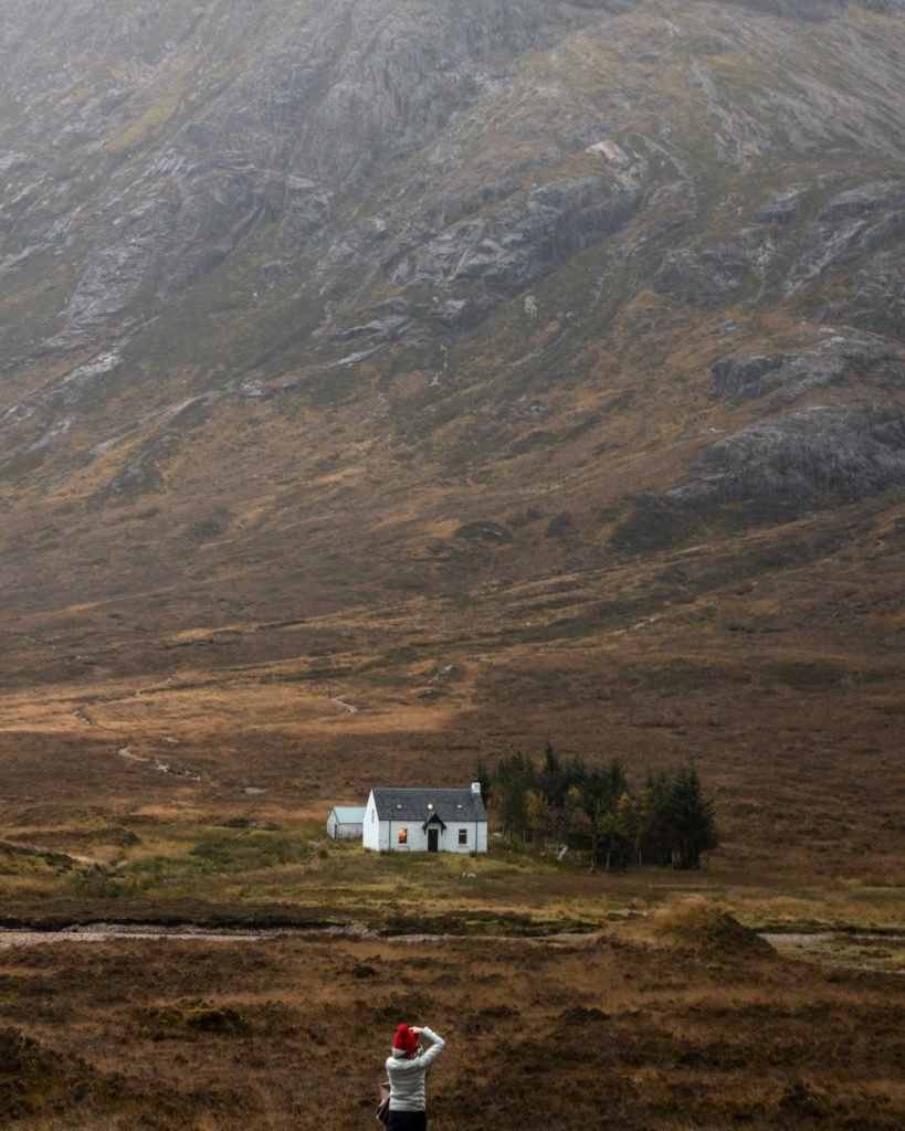 During our scouting trip across Scotland, Conor photographed this behind-the-scenes image of Zoe Timmers as she photographs a dramatic scene in the highlands. Int he background, a small country house is set against a rugged mountain vista.