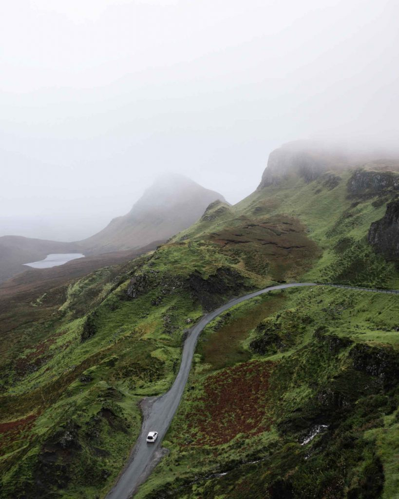 Scotland is home to dramatic landscapes, and they're often highlighted with moody weather. In this image of the Quirang, a car is seen driving on a rugged mountain road as fog rolls across the landscape.