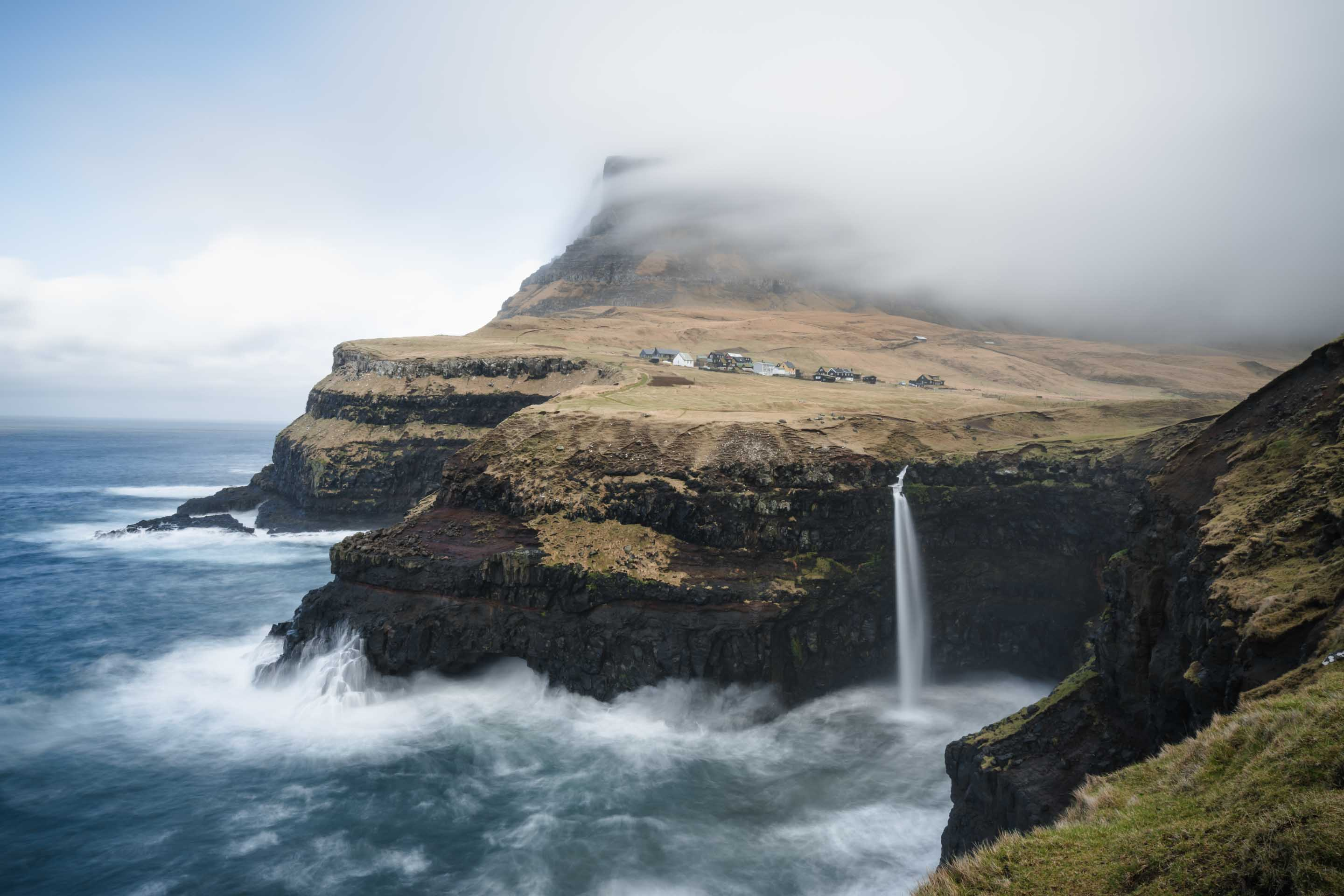 Easily one of the most photographed locations in the Faroe Islands, the Mulafossur waterfall plunges into the sea. Directly behind the waterfall is the small village, Gasadalur, and beyond it a large mountain. The scene is stunning, especially with dramatic ocean weather.