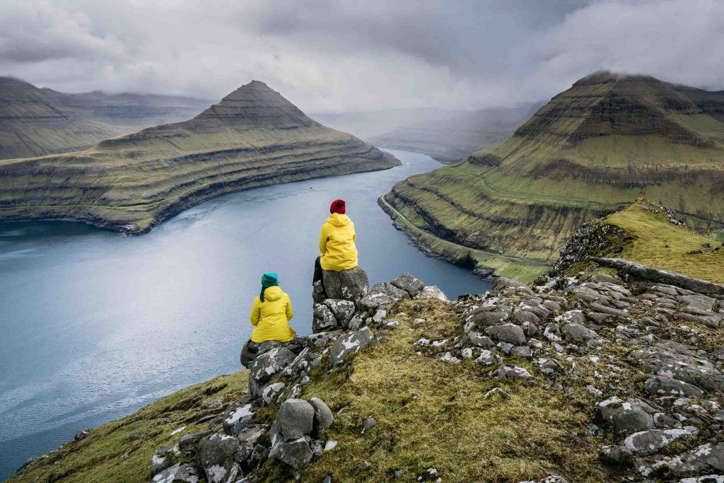 Workshop leader Zoe Timmers and a participant sit overlooking a fjord. Their matching yellow raincoats add to the scene, revealing the weather encountered while exploring this vast landscape.