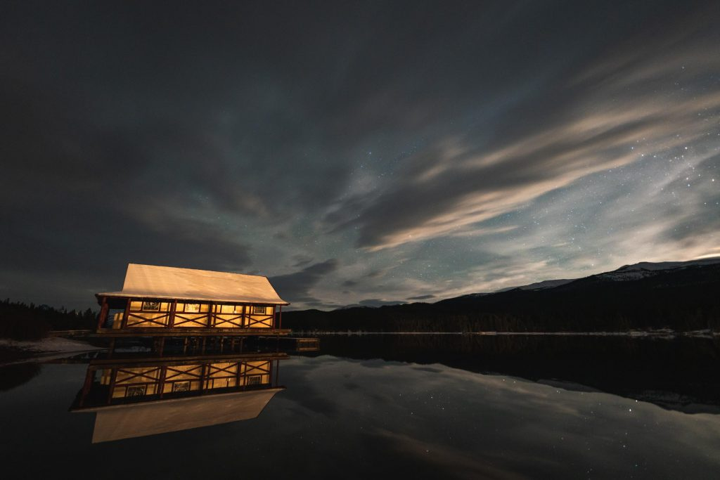Despite a partially cloudy sky, the Maligne Lake Boathouse stills stand out beneath a star filled sky. The open lake reflects the scene perfectly.