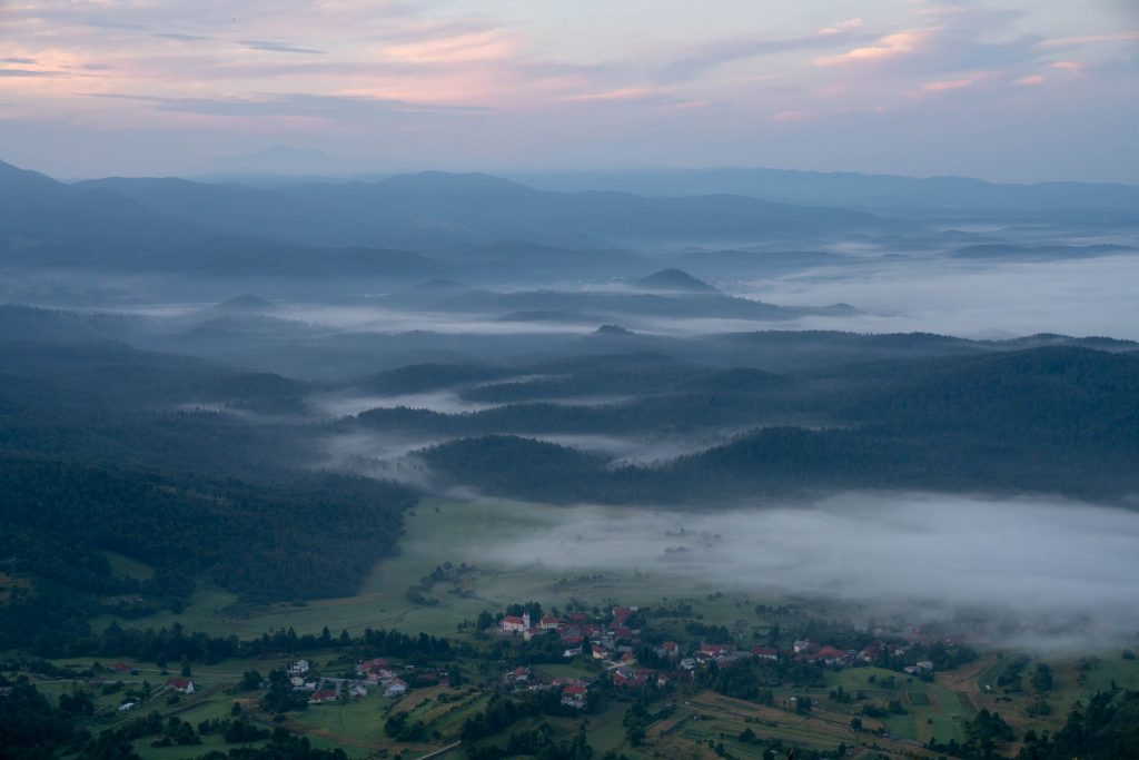 Early morning sunlight creeps across a rural farmers meadow in Slovenia, photographed from a high perch on Nanos Mountain on the Via Dinarica White Trail.