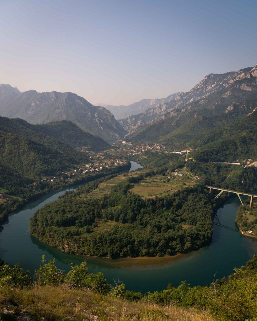 A stunning river valley, just outside Jablinica, Bosnia, highlights the natural landscape. The river forms a giant S curve with small villages along its shoreline. In the distance, dramatic mountains wouldn't look out of place in Switzerland, yet it's an unknown area in the Balkans.