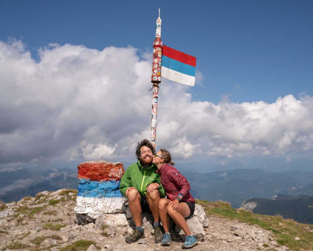 Two hikers celebrate reaching the top of Maglic, the highest peak in Bosnia and along the Via Dinarica White Trail that stretches across the Balkans. The hikers are sitting down in front of a summit monument celebrating the former Yugoslavia state.