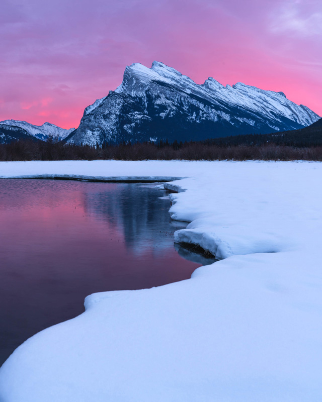A spectacular sunrise illuminates Mt Rundle and its reflection on Vermilion Lake in Banff National Park