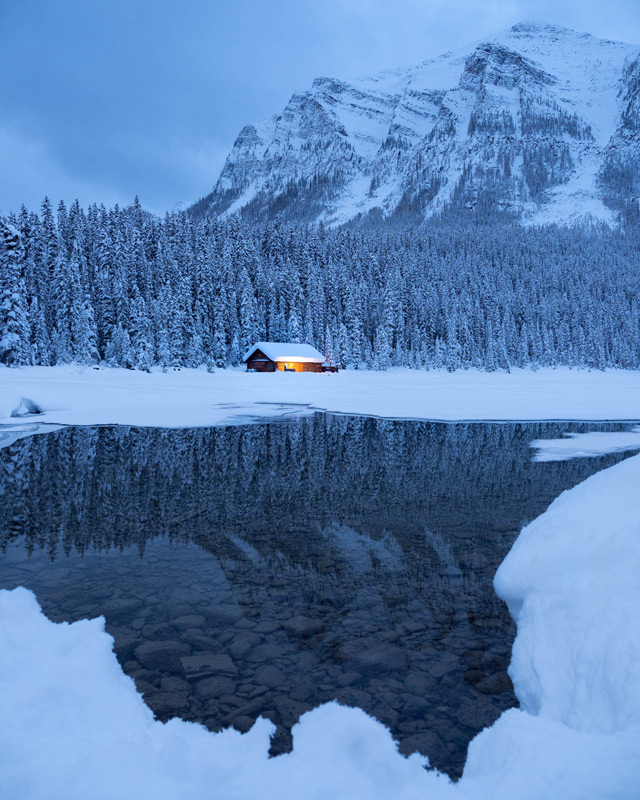 The classic pre-dawn images of Lake Louise, highlighting the iconic boathouse amid the winter landscape.