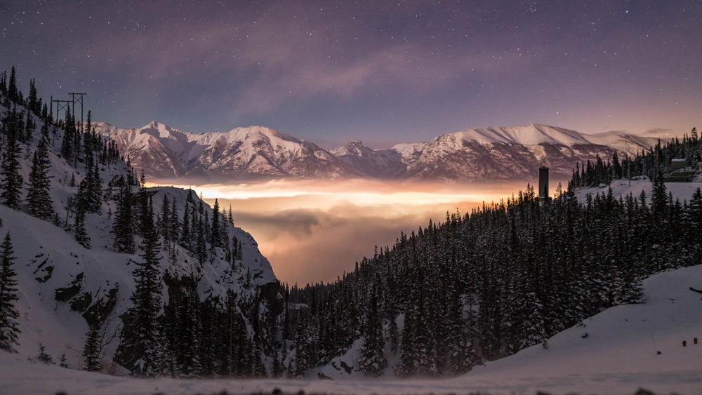 A stunning inversion blankets the town of canmore, alberta, in a thick fog. The night sky is visible above.
