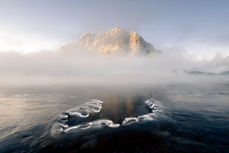 Sunrise strikes the Canadian Rockies, piercing a thick fog above Bow Lake in Banff National Park in Alberta, Canada.