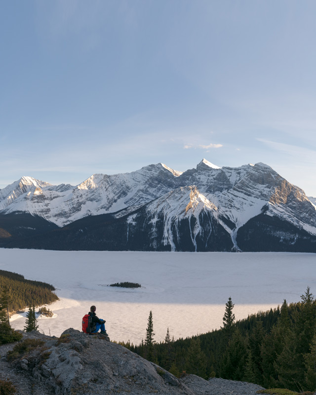 A hiker stands before Upper Kananaskis Lake, showing how a wide angle lens can be used to emphasize the scale of a landscape.
