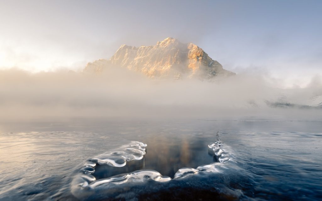 Ice cracks, along the edge of Bow Lake, make the ideal foreground for this scenic sunrise image. A thick fog nearly blocks the view of the Canadian Rockies, but the piercing sunrise illuminates the dramatic scene in Banff National park.