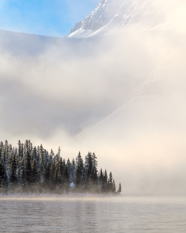 Using a telephoto lens to compress the scene at Bow Lake, I created an image that shows the sunlight filtering through thick fog to illuminate the Crowfoot Glacier and surrounding spruce forest.