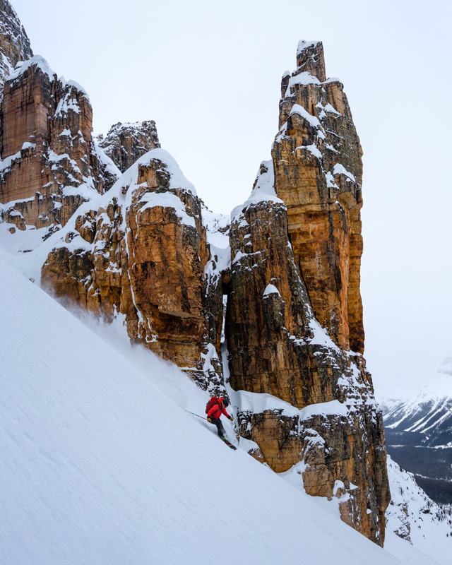 A skier descends past a rock spire on Bow Peak in the Canadian Rockies at the base of a coulouir called Grand Daddy.