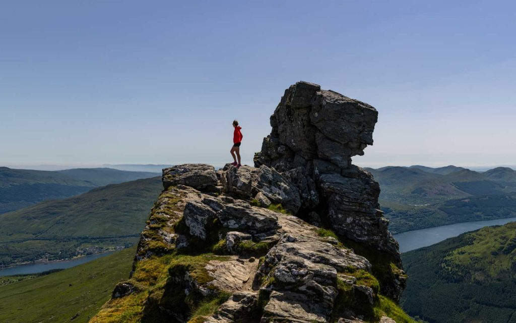 A 50 mm panorama of a hiker reaching the top of a Munroe peak in Scotland.