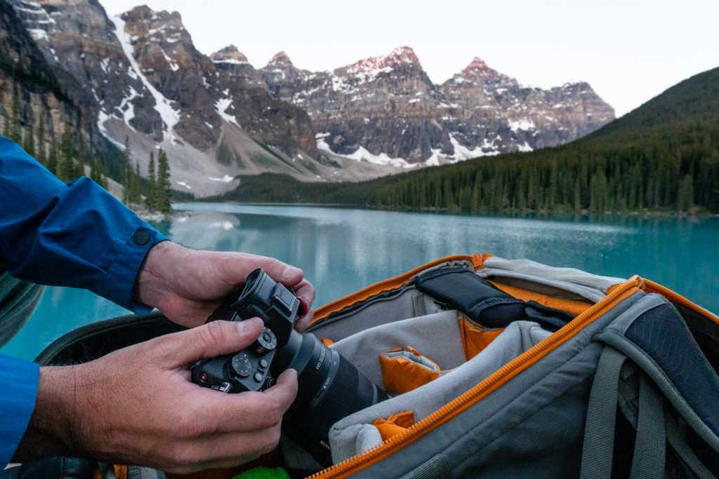Along the shore of Maligne Lake, I am pulling my Sony A7riii from my camera bag. The camera is just one item on my definitive photo and video equipment list.