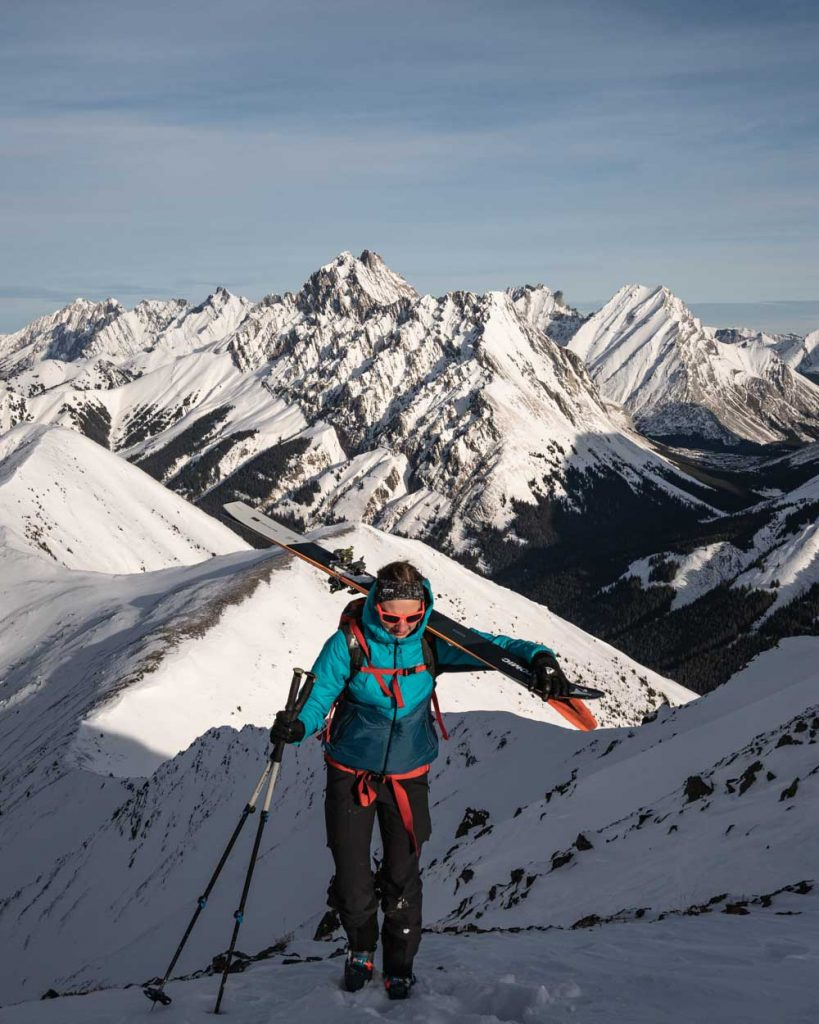 A skier hikes towards a mountain summit, wearing Eddie Bauer Equipment